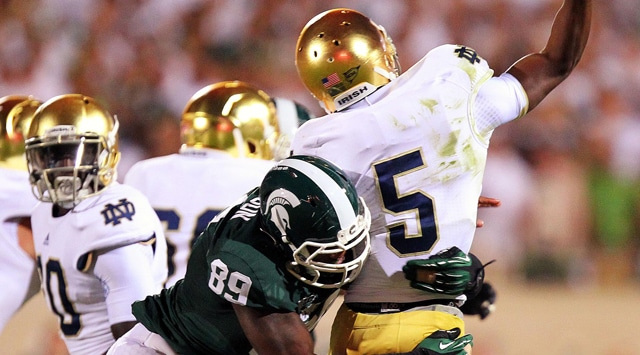 Notre Dame Fighting Irish quarterback Everett Golson (5) is sacked by Michigan State Spartans defensive end Shilique Calhoun (89) during the first half at Spartan Stadium. (Photo - Mike Carter / US PRESSWIRE)