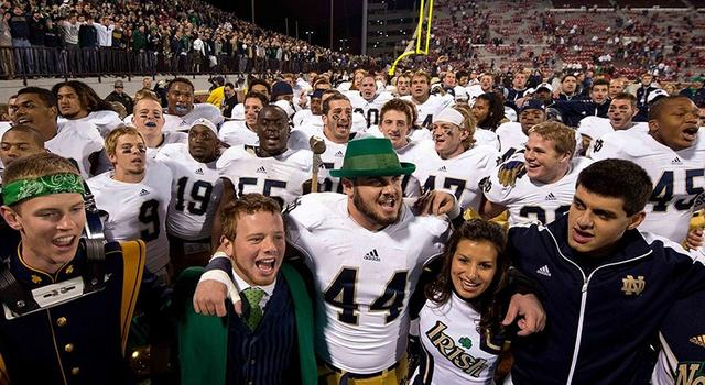 Oct. 27, 2012; Norman, OK, USA; Notre Dame Fighting Irish linebacker Carlo Calabrese (44) sings the Notre Dame alma mater with the Notre Dame leprechaun after Notre Dame defeated the Oklahoma Sooners 30-13 at Oklahoma Memorial Stadium. Mandatory Credit: Matt Cashore-US PRESSWIRE
