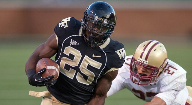 Wake Forest Demon Deacons running back Josh Harris (25) runs the ball while being pursued by Boston College Eagles defensive back Justin Simmons (27) during the third quarter at BB&T field. Wake Forest defeated Boston College 28-14. (Photo: Jeremy Brevard-US PRESSWIRE)