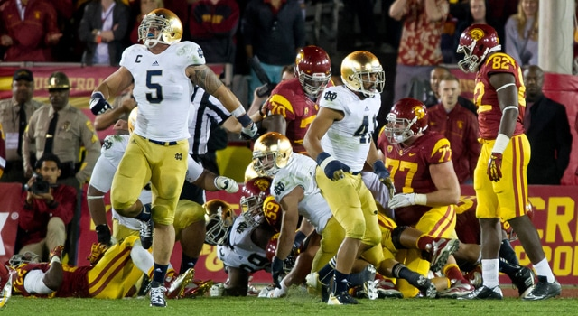 Notre Dame Fighting Irish linebacker Manti Te'o (5) and safety Matthias Farley (41) react after stopping USC Trojans tailback Curtis McNeal (22) near the goal line in the fourth quarter at the Los Angeles Memorial Coliseum. Notre Dame won 22-13. Mandatory Credit: Matt Cashore-USA TODAY Sports